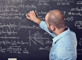 Man writing complicated formulas on a blackboard with chalk.