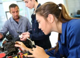 Female apprentice working on an engine