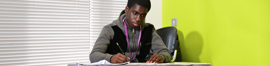Male student writing at a desk