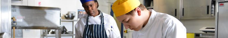 A catering tutor and their student preparing food