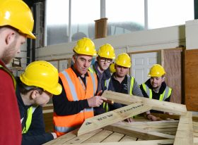 Male construction teacher measuring wood with male students watching