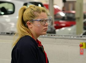 Female engineering apprentice using machinery