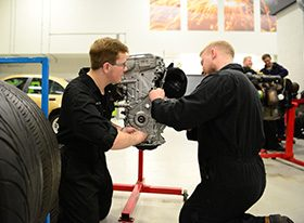 Two male students working on engine
