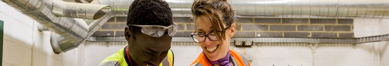 Female construction teacher and male student smiling and working together