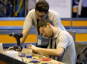 Two male engineering apprentices with drill