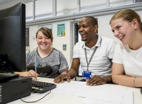 Male teacher and two female learners looking at computer screen and smiling