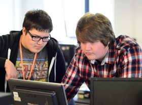 Students collaborating at computer screen
