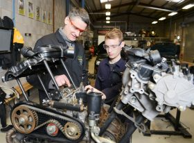 Employer and student working on engine