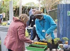 student with SEND gardening with teacher gardening