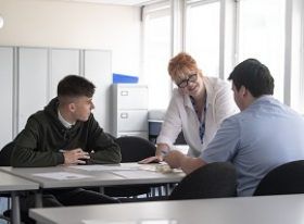 Female teacher with two male students