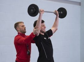 Sport teacher supporting student doing shoulder press