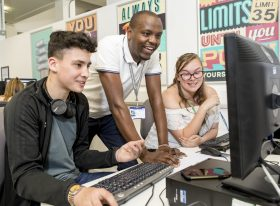 tutor with students at computer screen