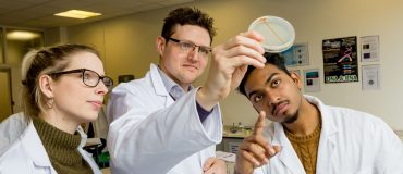 Science teacher and students look at petri dish