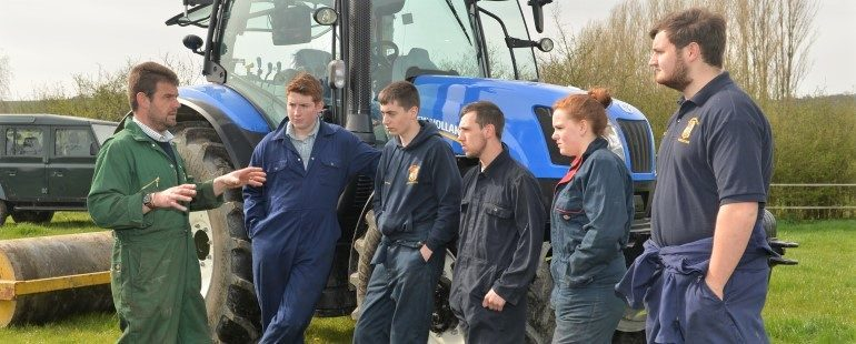 Teacher with students in front of tractor