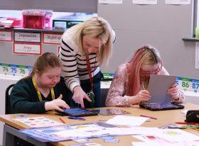 teacher helping SEND students in classroom