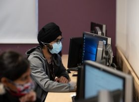Male student wearing a face mask whilst on the computer