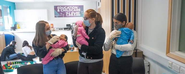 three girls in face masks with demonstration babies in Education and Childcare T Level class