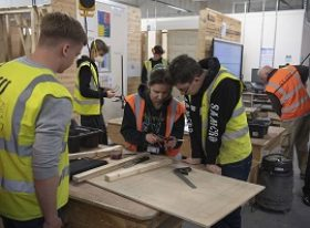 Carpentry tutor with two learners in workshop