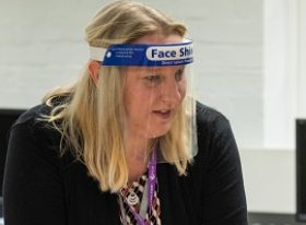 Female teacher wearing a plastic face shield